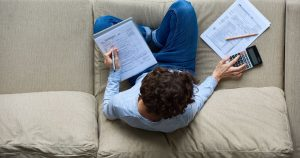 Man sitting on the couch working on his taxes